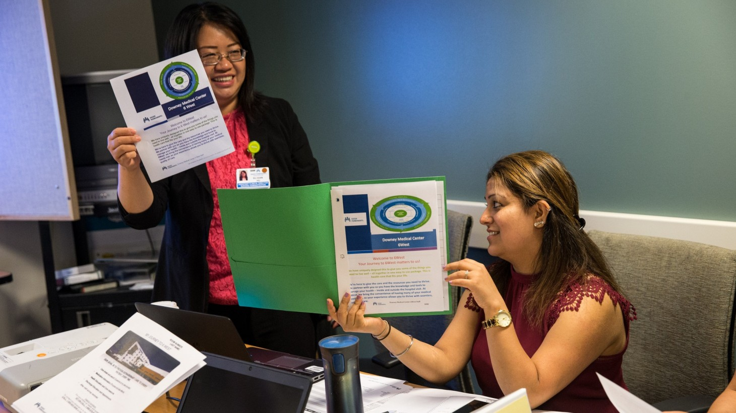 two women at a meeting table, holding up documents