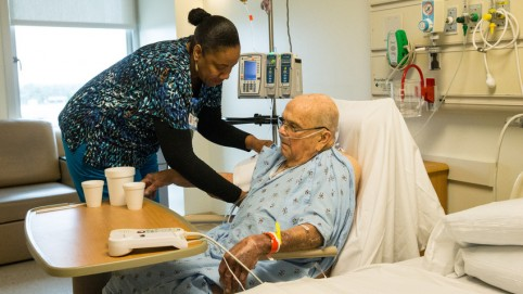 Caregiver with elderly patient in a hospital room