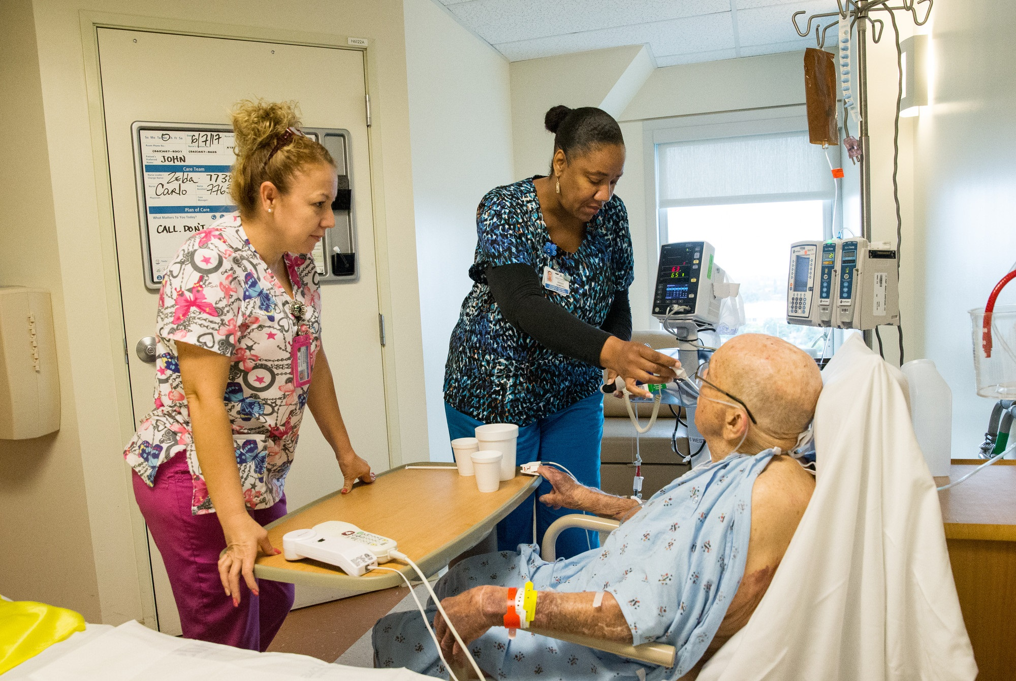 Two caregivers in a hospital room with an elderly patient
