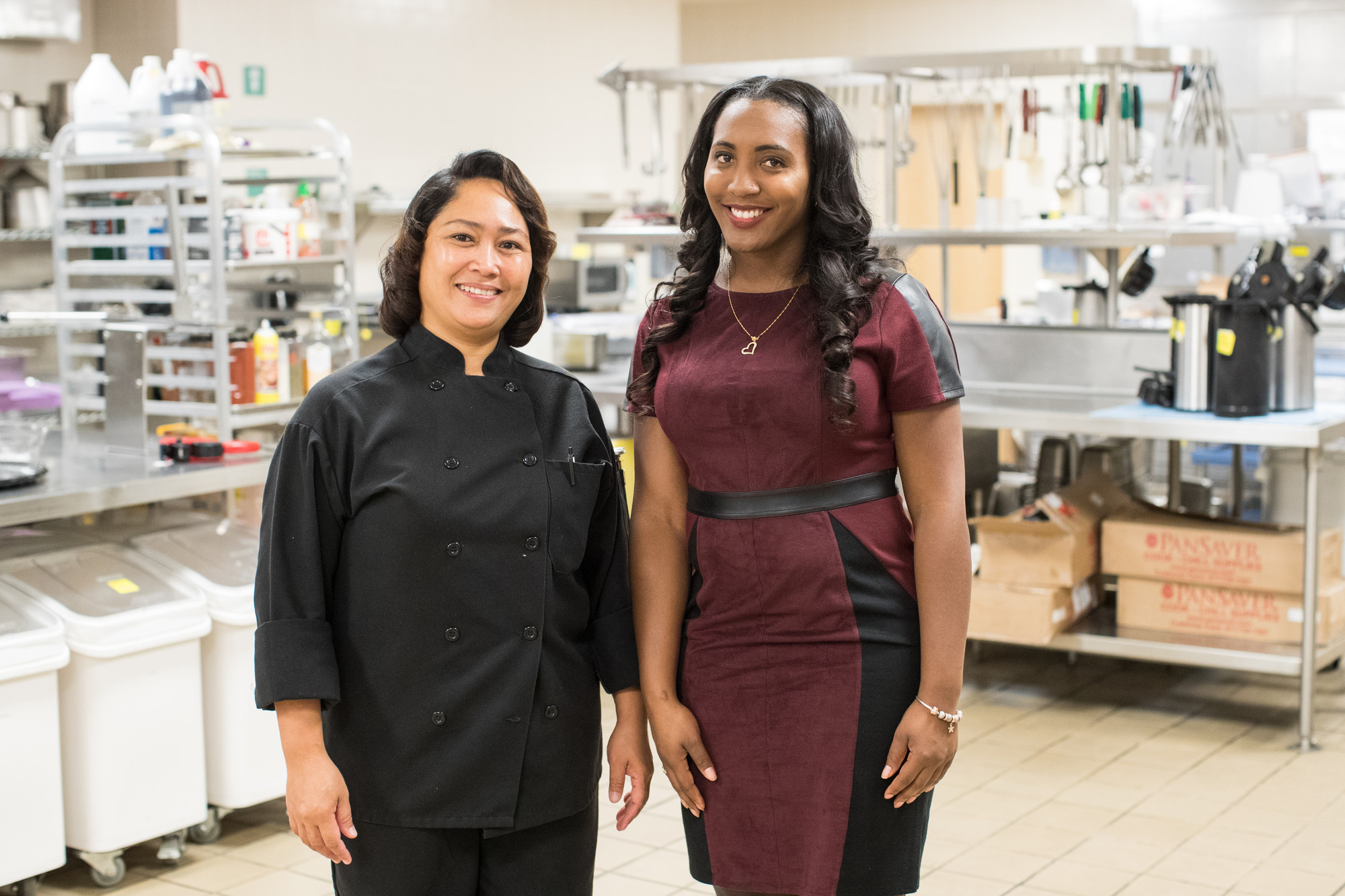2 women (one wearing a black chef's jacket) in an industrial kitchen