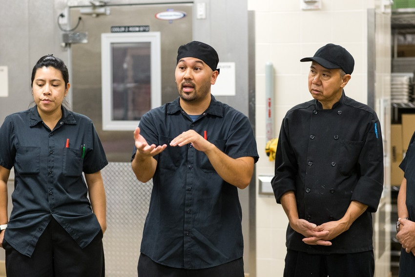 3 kitchen workers dressed in black discussing a serious issue