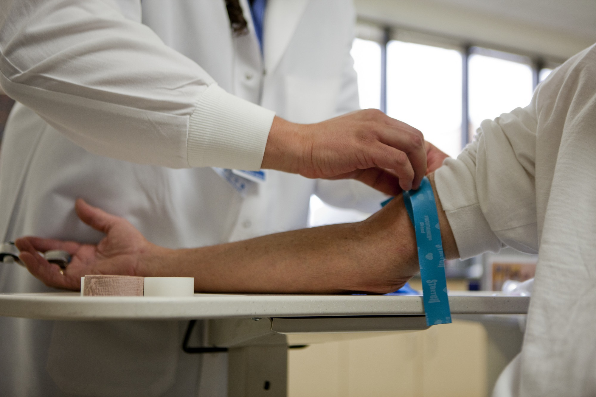 A provider preparing a patient's arm for a blood draw