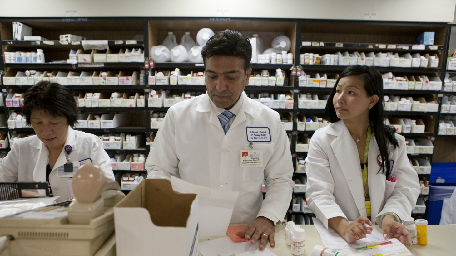 Three pharmacy workers working in front of a wall of medications