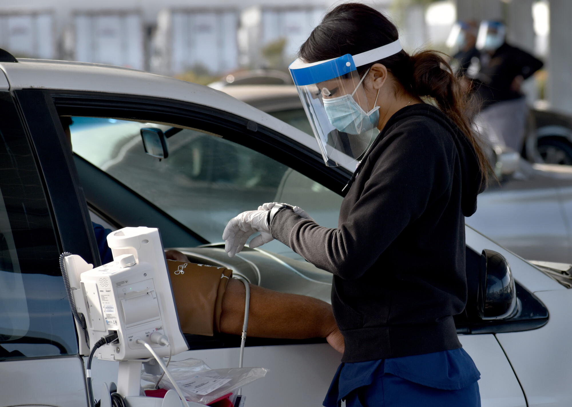 Woman wearing face shield checking a man's blood pressure while he sits in the passenger seat of a car