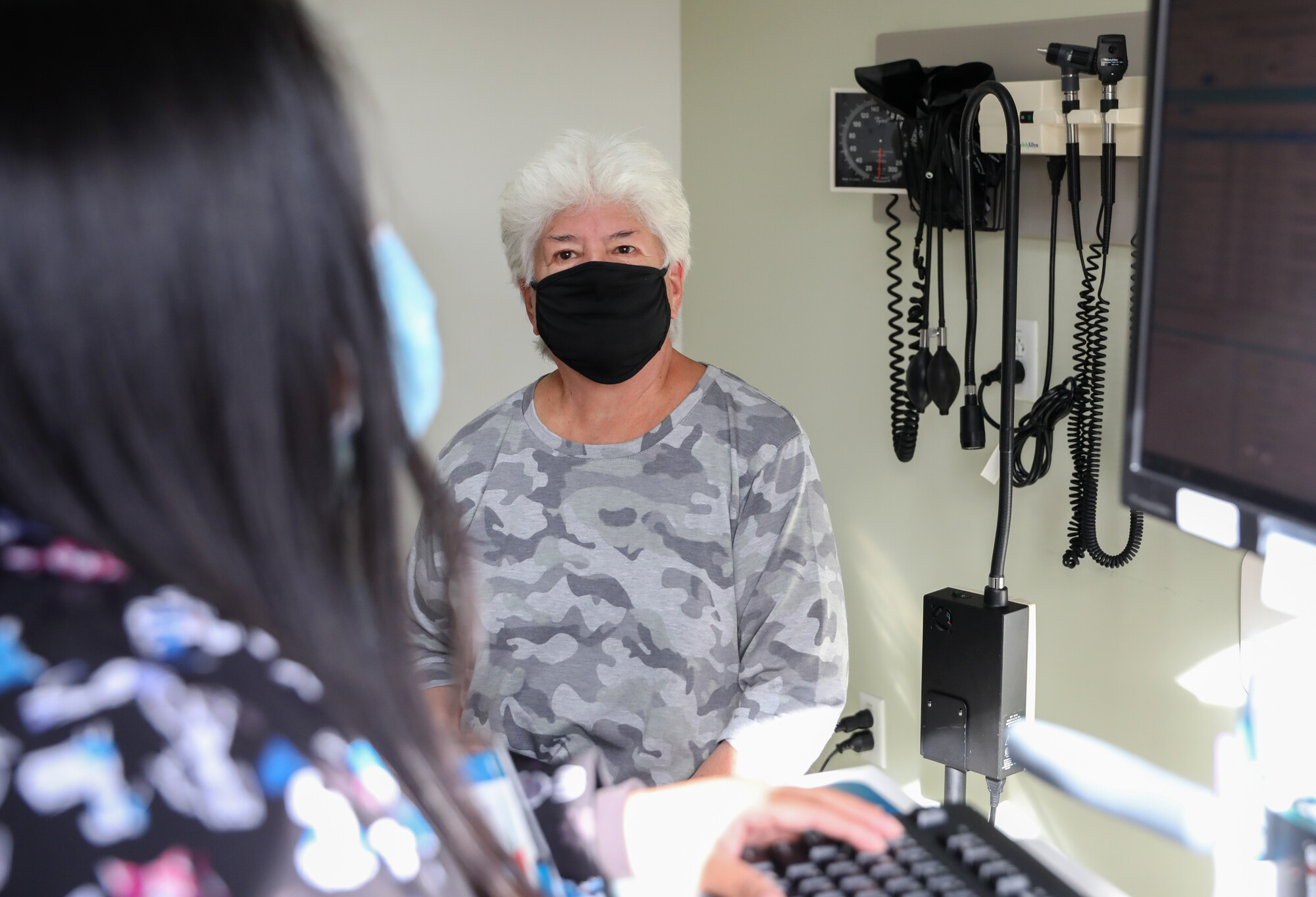 Elderly female patient in a doctor's office, wearing a mask