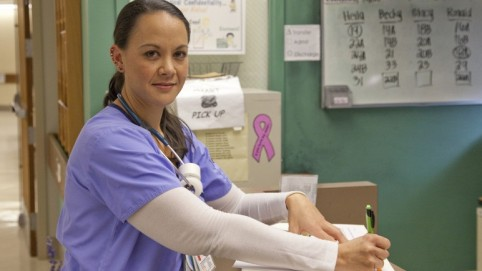 Nurse at a nurses' station writing down notes
