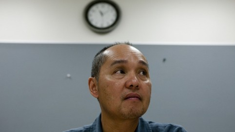 Anxious-looking man sitting under a clock