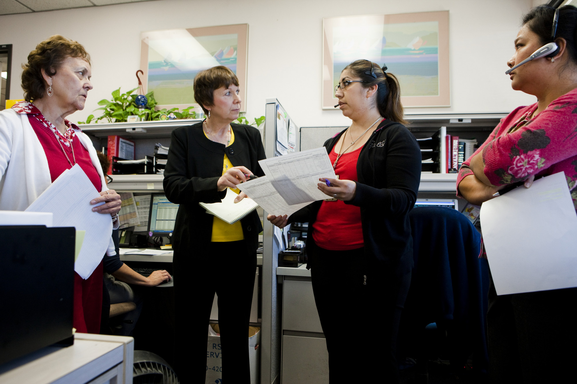Four female health care workers standing in their morning huddle