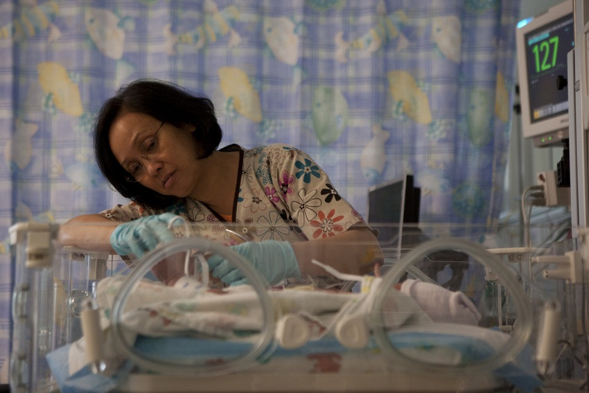 Nurse tends to an infant in an incubator