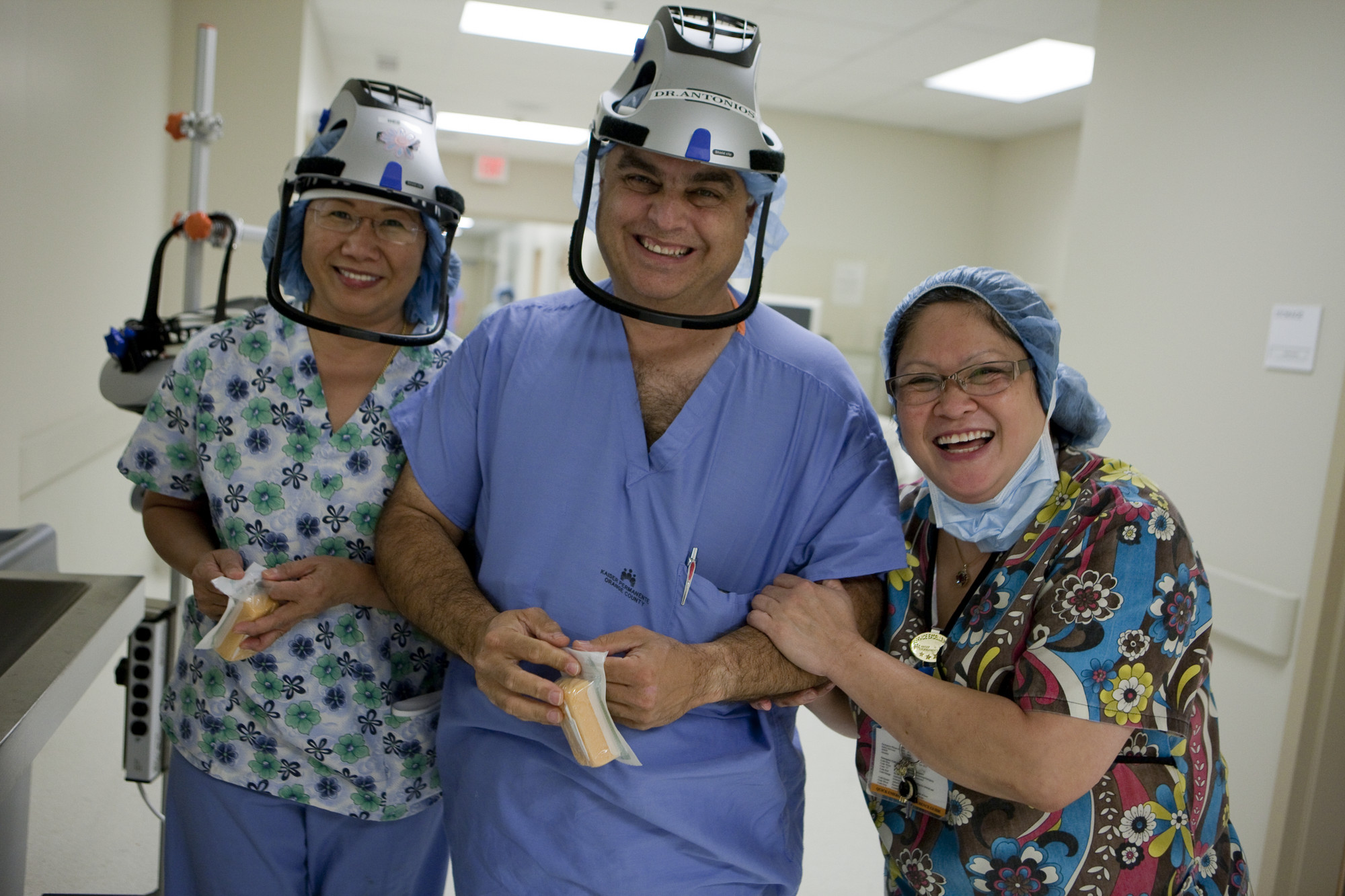 Three smiling health care workers, wearing interesting hats
