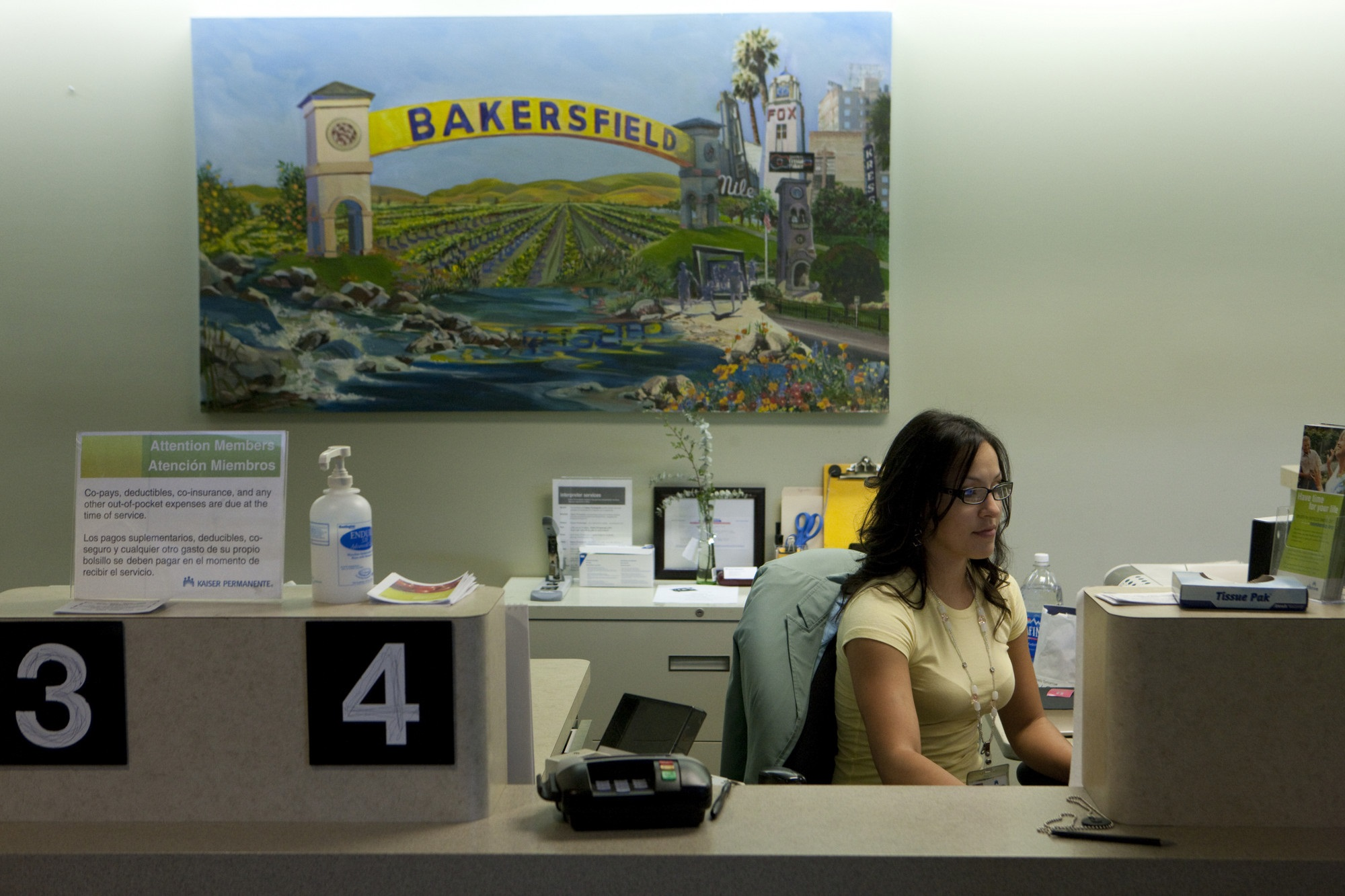 Receptionist at her desk under a painting of Bakersfield