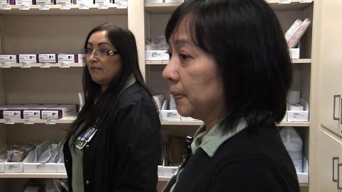 Two nurse examine supplies in their supply closet
