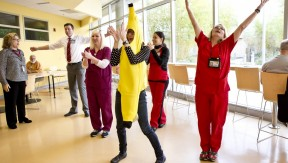 Health care workers (including one dressed a giant banana) exercising together