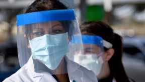 Two women in face shields and masks working at the drive-up hypertension clinic