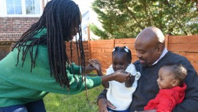 In a sunny backyard, a Black mom holds hands with her young daughter, who is sitting with her brother in the lap of their dad.