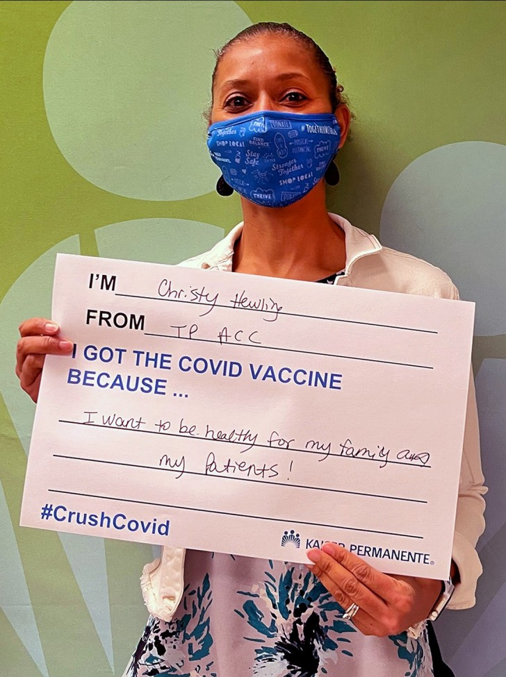 Female physician wearing a face mask and holding up a large sign