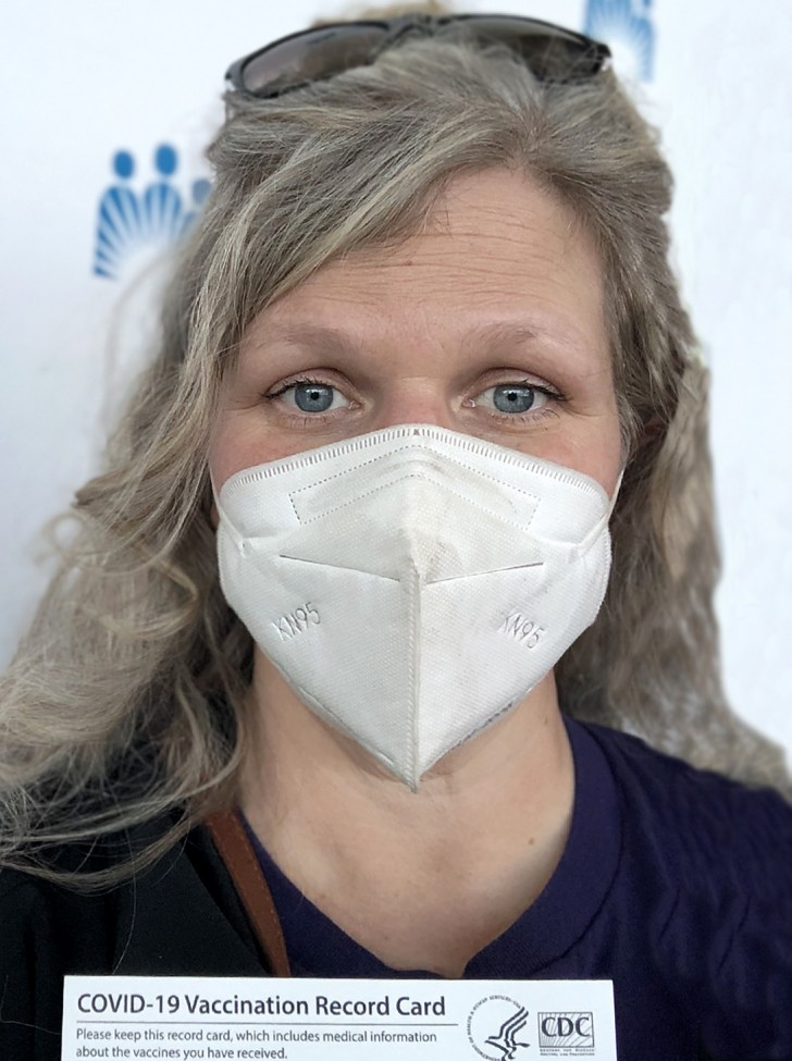 woman with blonde hair and blue eyes, wearing a white mask