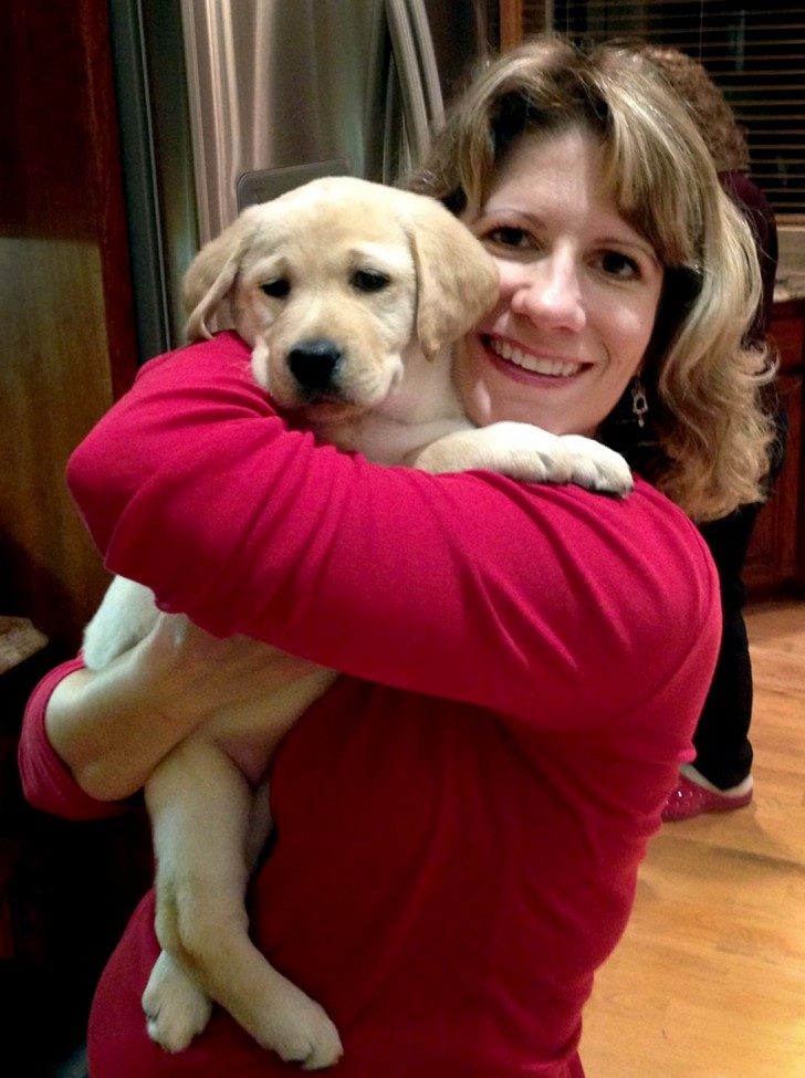 Woman wearing a red sweater holding a puppy