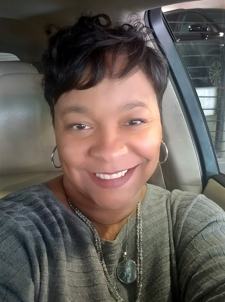 African American woman with a big smile sitting in a car.