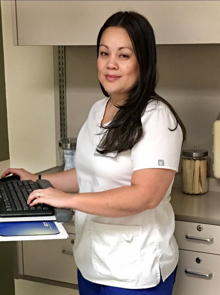 Female health care worker wearing white scrubs, standing at a computer keyboard