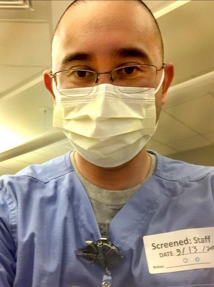 Portrait of a male health care worker in blue scrubs, wearing a mask