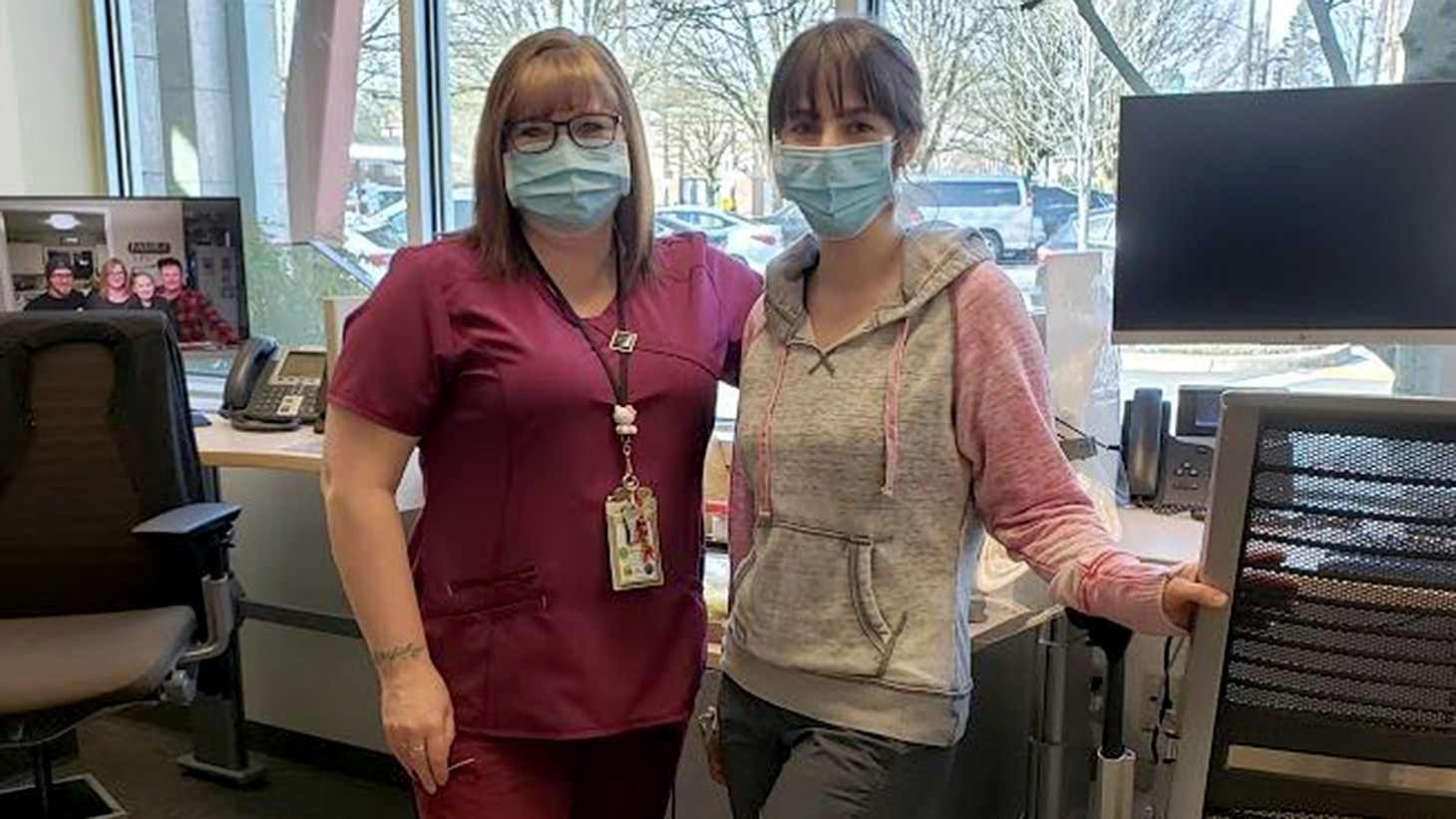 Two women, health care workers, posing together in an office