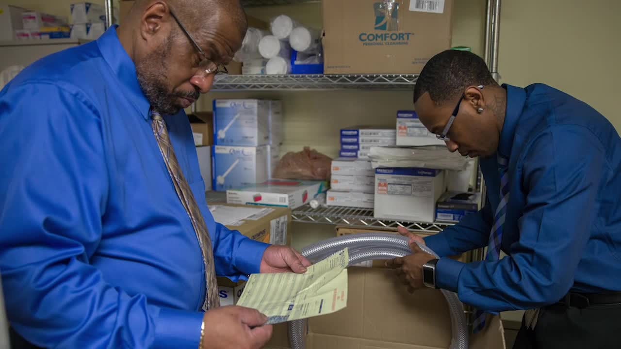 Two men in blue shirts examing packages in a supply room