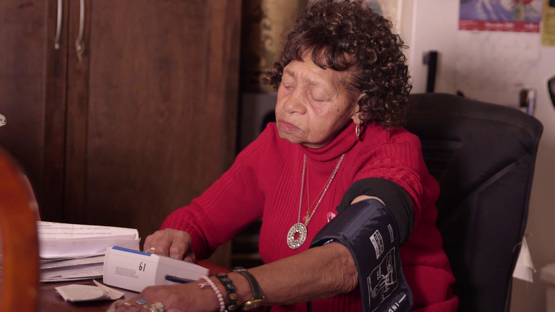 Elderly woman checks her blood pressure in her own home
