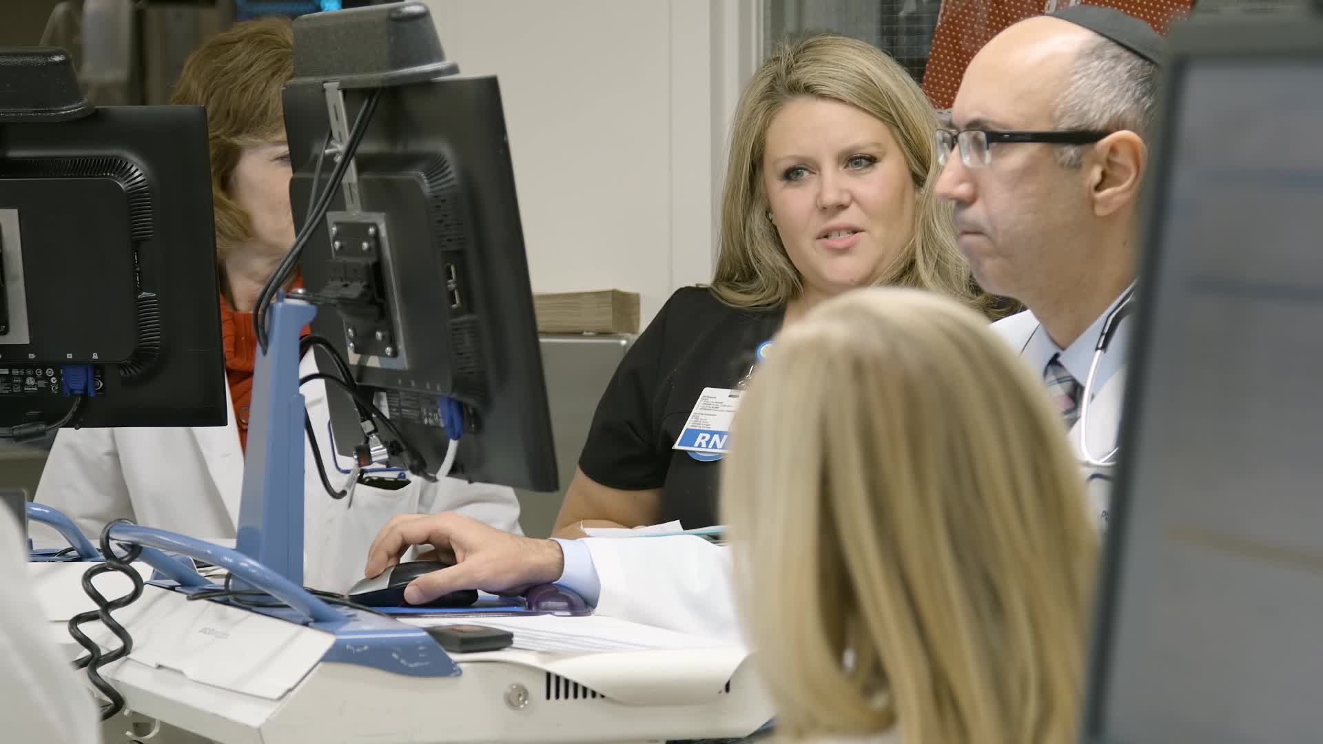 Doctors and nurses huddle around a computer