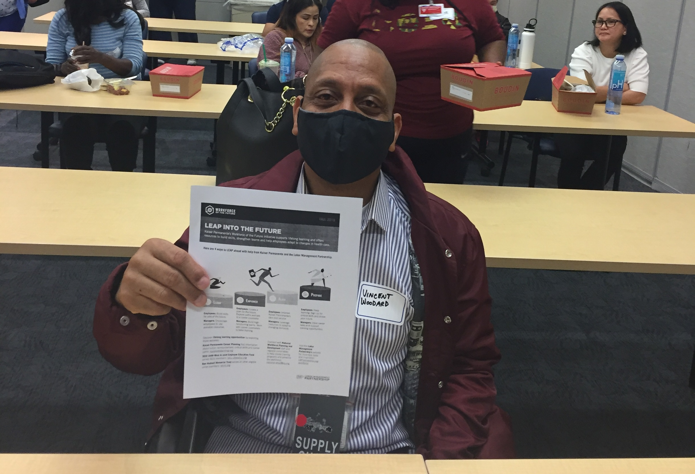 A black man, wearing a mask, holding up a flier